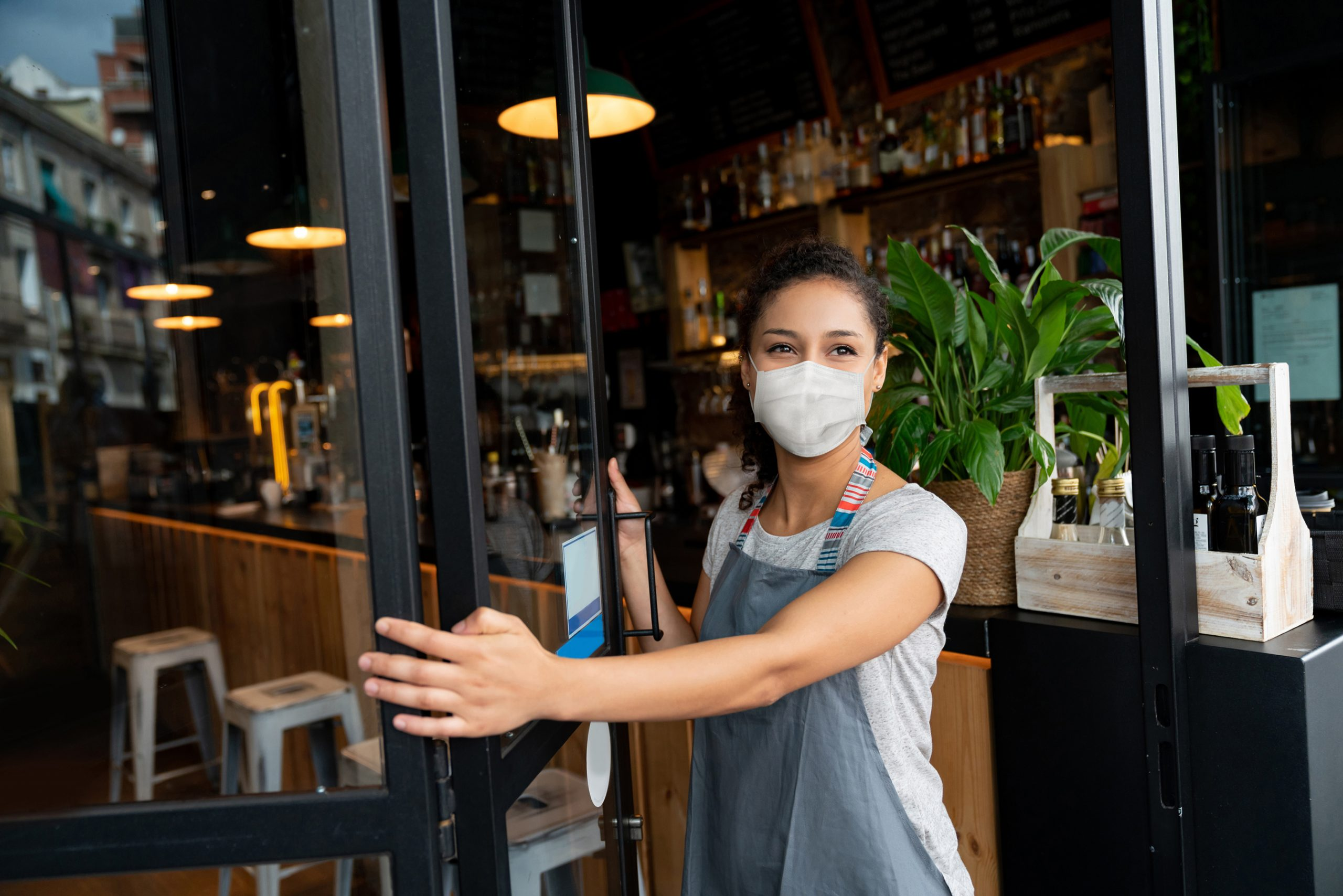Happy business owner opening the door at a cafe wearing a facemask to avoid the spread of coronavirus â?? reopening after COVID-19 concepts