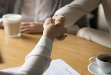 Couple handshaking businesswoman making investment deal in cafe, clients customers agree to sign contract shaking hands with mortgage insurance broker, estate agent or lawyer, close up view